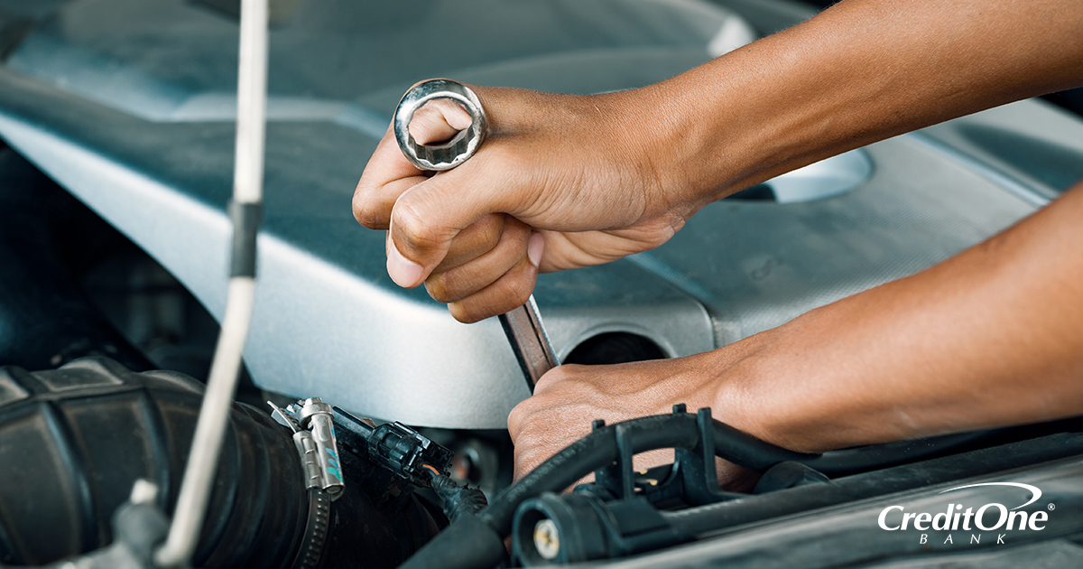 A pair of hands using a wrench to apply a quick repair to a car engine