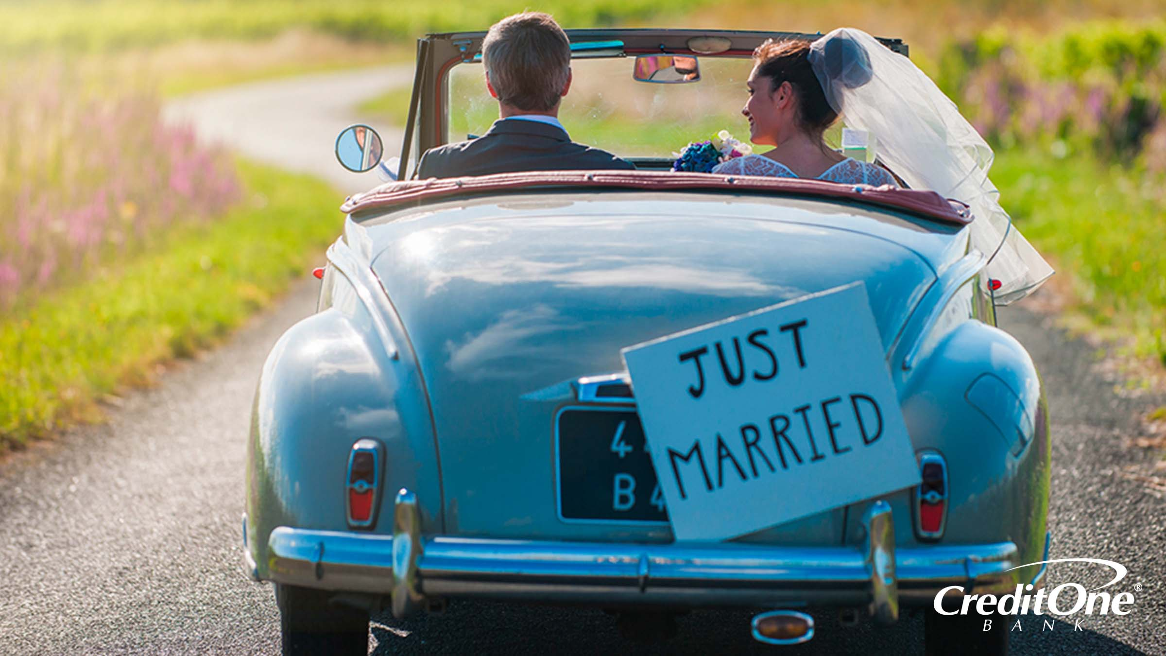 A newly married couple driving away together with a 'Just Married' sign