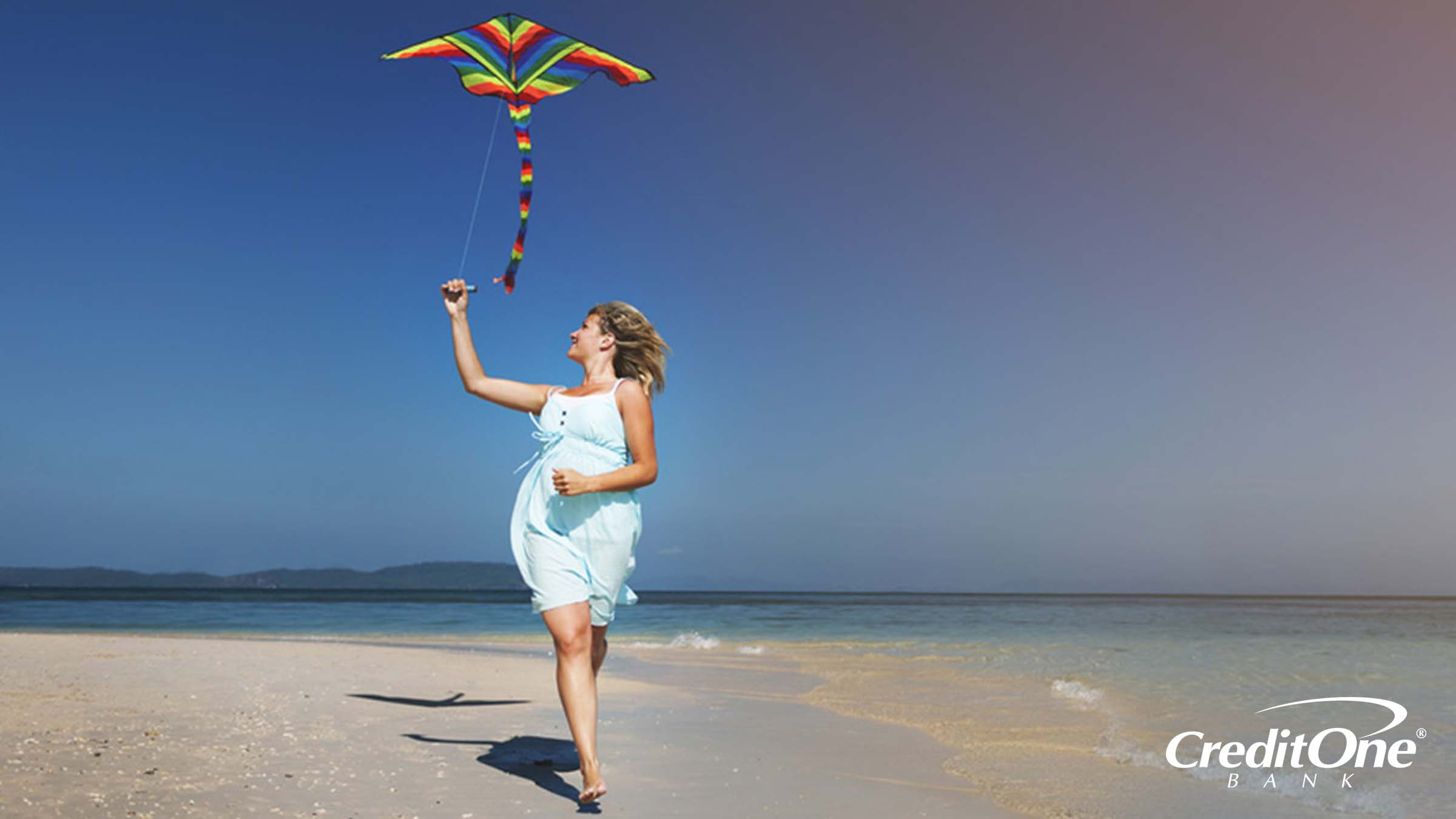 Woman running on a shoreline with a kite flying overhead