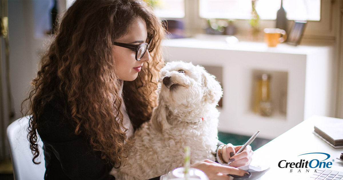 Woman with a dog in her lap calculating her finances on a computer